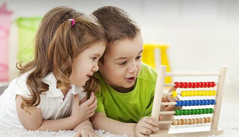 zdjęcie chłopca i dziewczynki bawiących się liczydłem