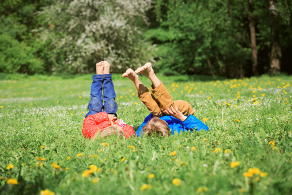 zdjęci dzieci leżących na trawie z uniesionymi nogami