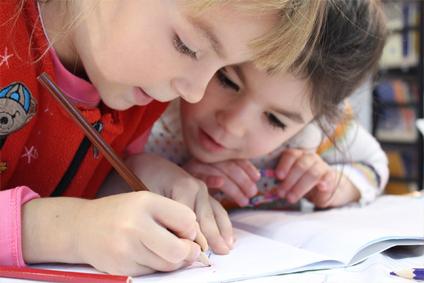 zdjęcie dwóch dziewczynek rysujących w zeszycie